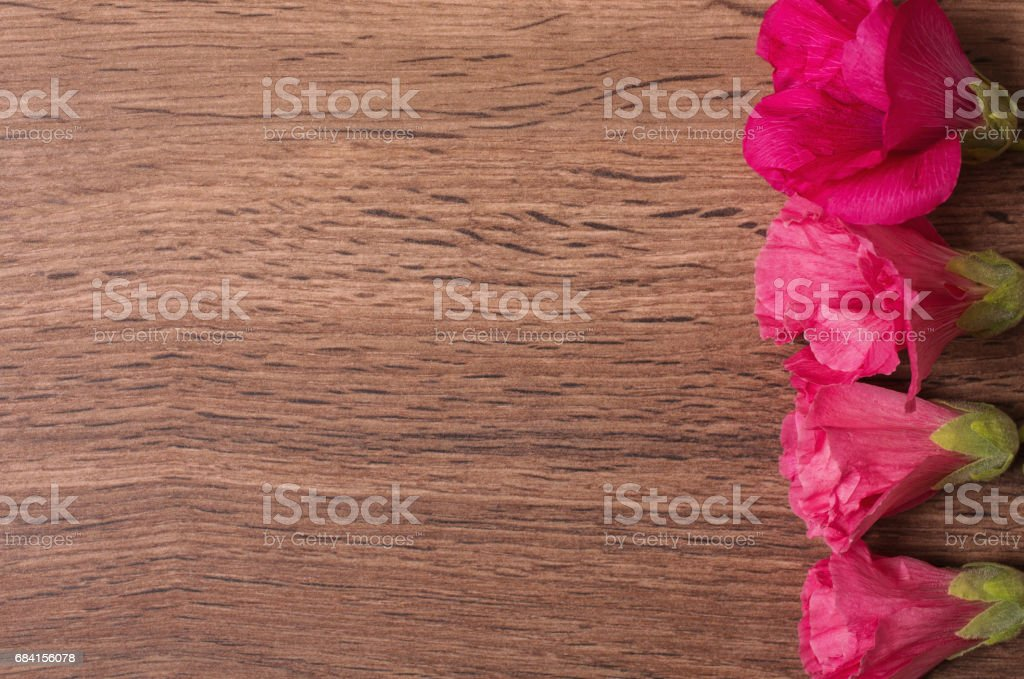Red flowers lie on the wooden background. Space for text and design. Copyspace, top view foto stock royalty-free