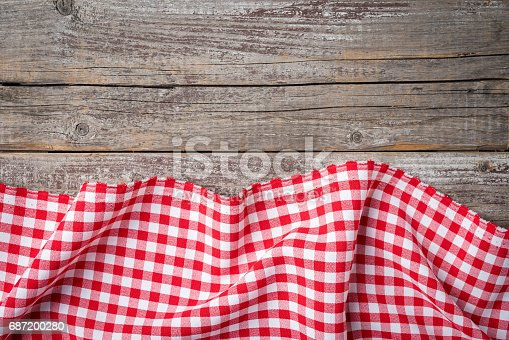 istock Red folded tablecloth on an old wooden table 687200280