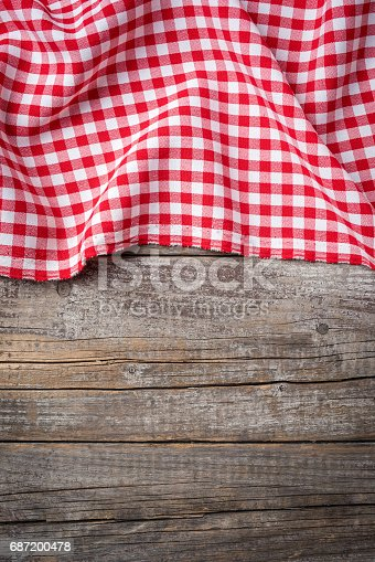 istock Red folded tablecloth on an old wooden table 687200478
