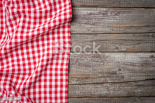 istock Red folded tablecloth on an old wooden table 687202894