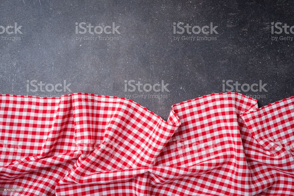 Red folded tablecloth on gray stone table. stock photo