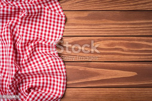 istock Red folded tablecloth on wooden table 670953876
