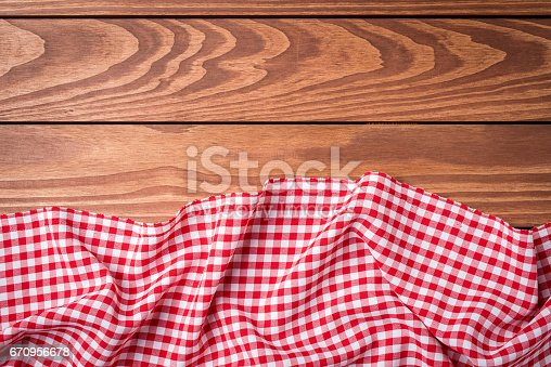 istock Red folded tablecloth on wooden table 670956678