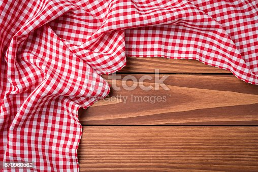 istock Red folded tablecloth on wooden table 670960562