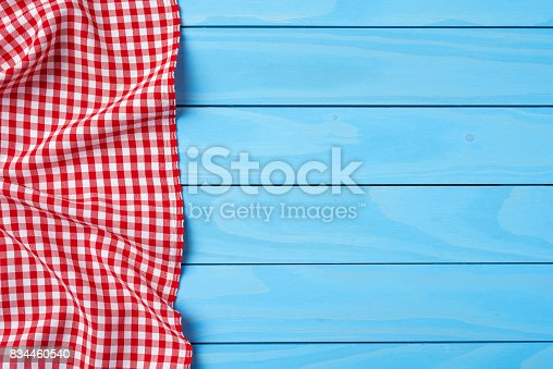 istock Red folded tablecloth over blue wooden table 834460540