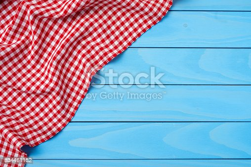 istock Red folded tablecloth over blue wooden table 834461182
