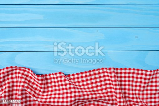 istock Red folded tablecloth over blue wooden table 834465520