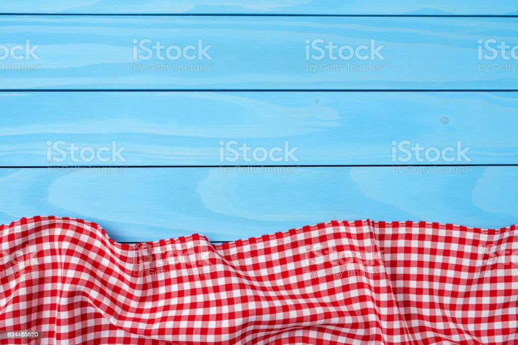 Red folded tablecloth over blue wooden table stock photo