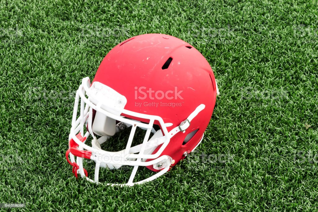 Red football helmet on a green turf field stock photo