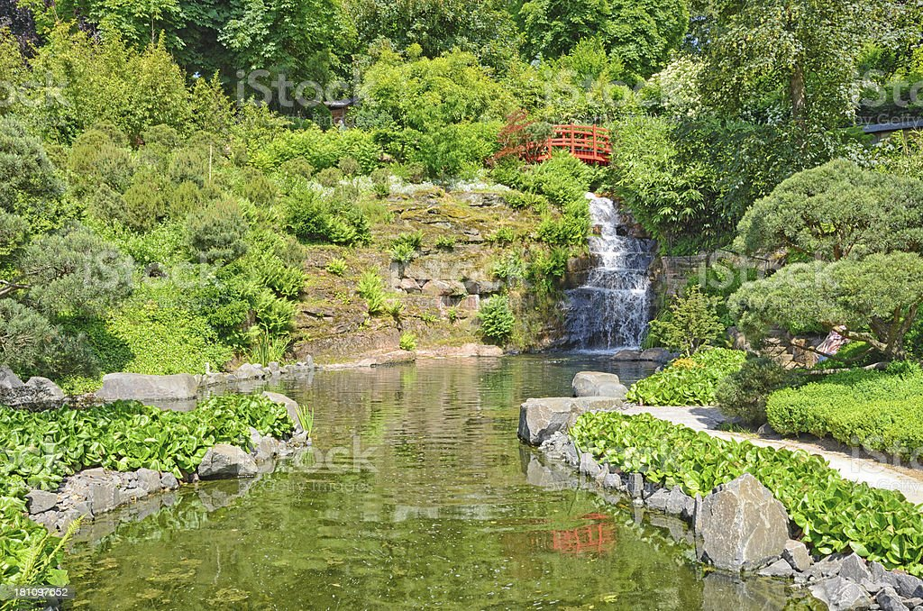 Red footbridge with waterfall and lake in japanese garden royalty-free stock photo