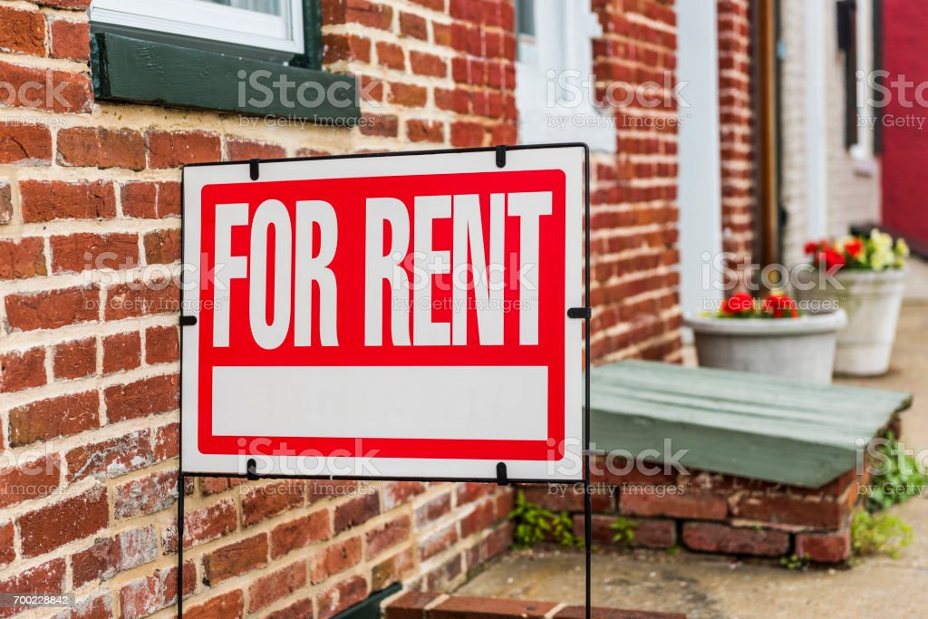 Red For Rent sign closeup against brick building royalty-free stock photo