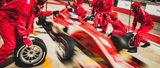 coche de carreras de fórmula roja dejando la parada en boxes - irl indycar series fotografías e imágenes de stock
