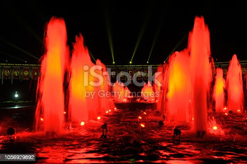 """MOSCOW, RUSSIA - Impressive fountains on Square of Victors spotted with red lights and testing video mapping projections on the facade of the Victory Museum on Poklonnaya Hill in the background in one day before beginning fascinating Moscow International Festival """"Circle of Light"""". The popular festival took place in the Victory Park first time on September 21-25, 2018."""