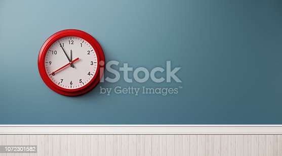 Red framed clock on blue wall. Horizontal composition with copy space.
