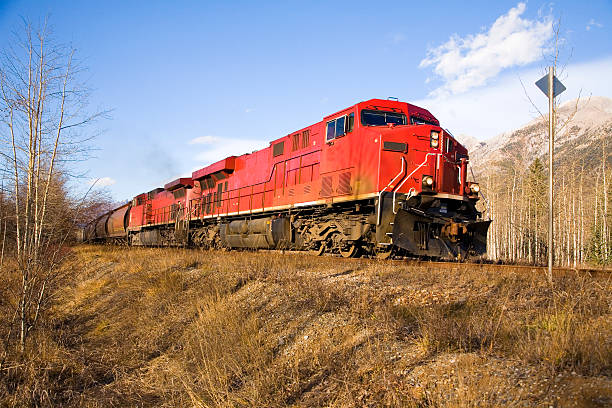 Red freight train traveling through dry landscape stock photo