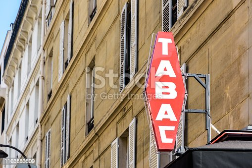 Red french tobacco shop sign with white lettering and a building in the background.