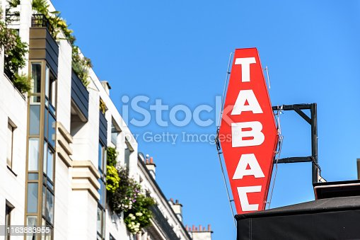 Red french tobacco shop sign with white lettering and modern building in the background against blue sky.