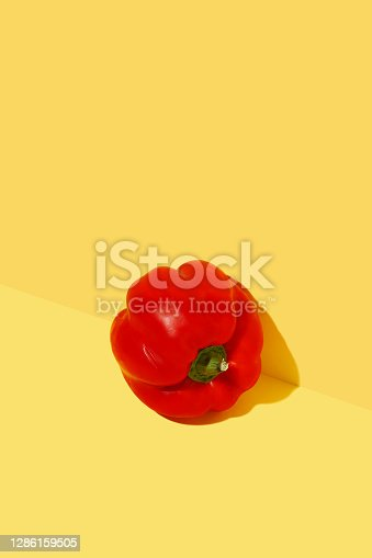 Red fresh bell pepper on bold yellow background. Minimal trendy composition. Healthy organic vegan food concept