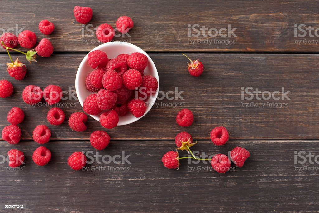 Red fresh raspberries on brown rustic wood background - foto de stock