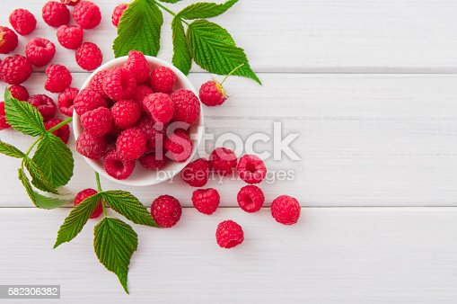 istock Red fresh raspberries on white rustic wood background 582306382