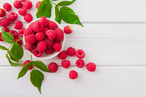 istock Red fresh raspberries on white rustic wood background 582306382
