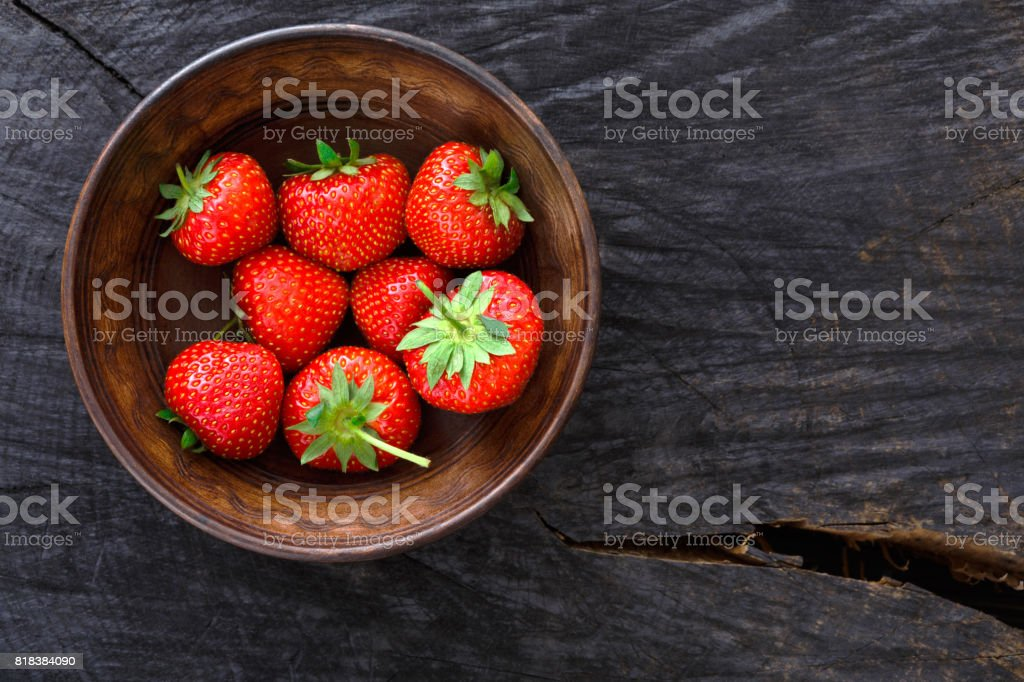 Red fresh strawberries on black rustic wood background stock photo