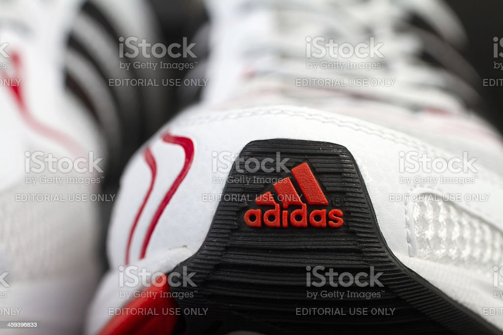 Red front Adidas logo on white running shoe stock photo