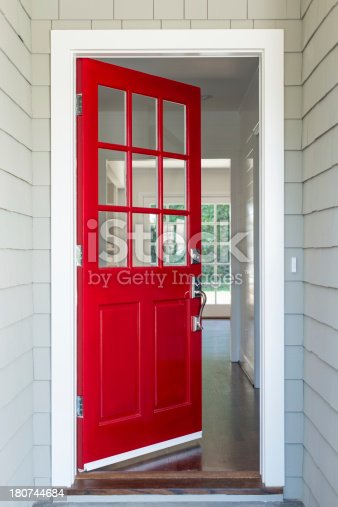 Front entrance to a residential home with a red solid wood door. The surrounding walls are covered with shingles.