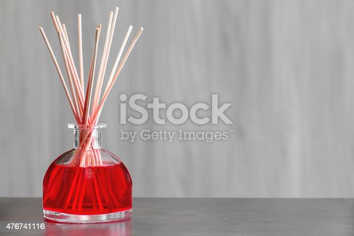 Air freshener, red fruits perfume diffuser shot with copy space on blurred wooden background. Air freshener, red fruits perfume diffuser and stems of reeds to spread a perfume slowly indoors. Object placed on gray table with blurred wooden background, horizontal shot photography.