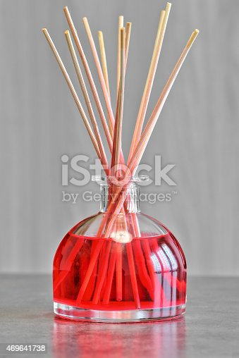 Air freshener, red fruits perfume diffuser and stems of reeds to spread a perfume slowly indoors. Object placed on gray table with blurred wooden background, vertical shot photography.