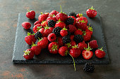 Heap of strawberries, raspberries and blackberries on a piece of slate.