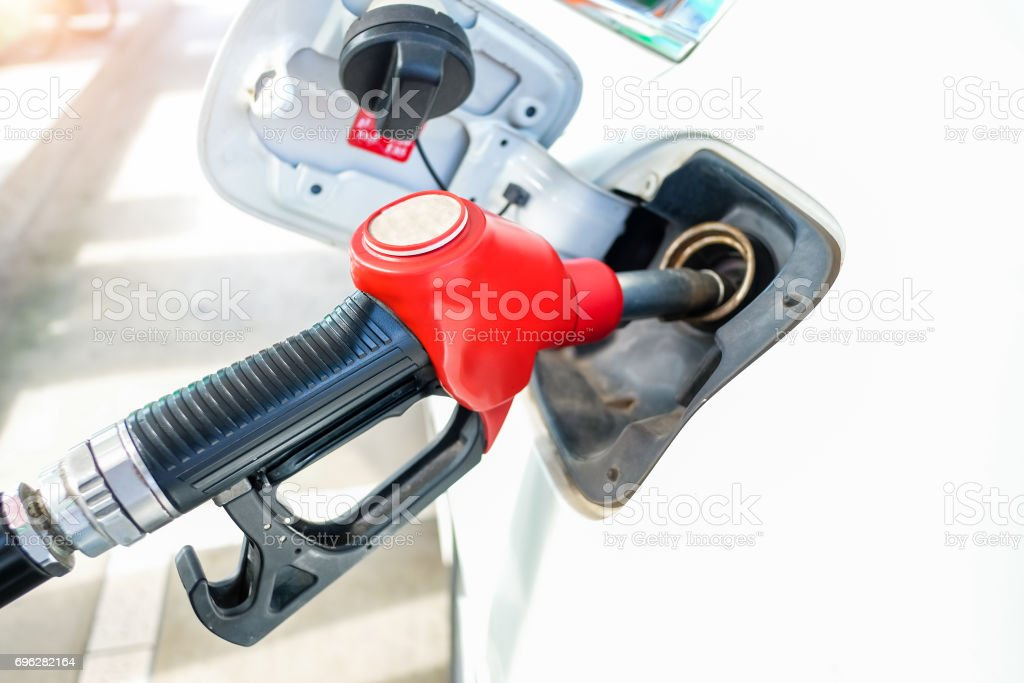 Red fuel nozzle in pouring to white car, Thai Petrol pump filling nozzles , Gas station in a service stock photo