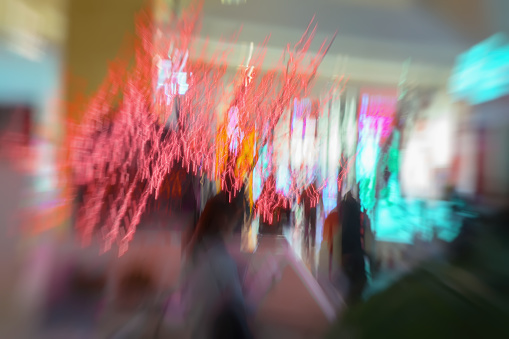 Red garland, christmas ornaments, in the shopping center, xmas, twinkle lights. Abstract defocused motion blurred unrecognizable people in shopping mall, holidays