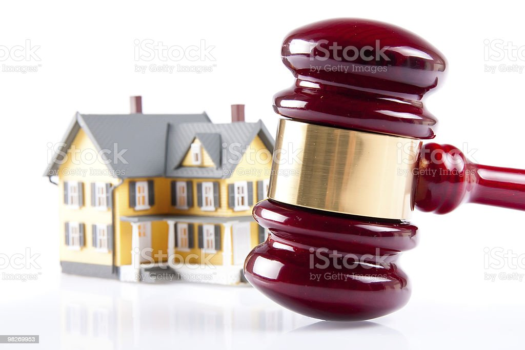 A red gavel with a small house in the background stock photo