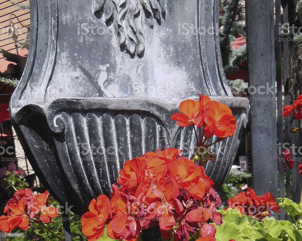 Red Geraniums and Iron Wall Fountain royalty-free stock photo