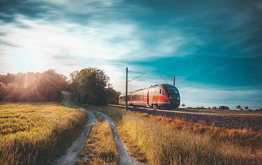 Red German train traveling on railway tracks through nature