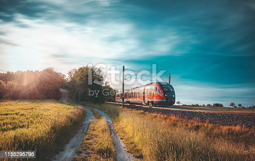 Red German train traveling on railway tracks through nature, near a rural alley, at sunset, near Schwabisch Hall, Germany. Travel concept.