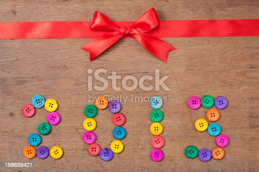 istock Red gift bow, New Year 2013 date on wooden background 158659421