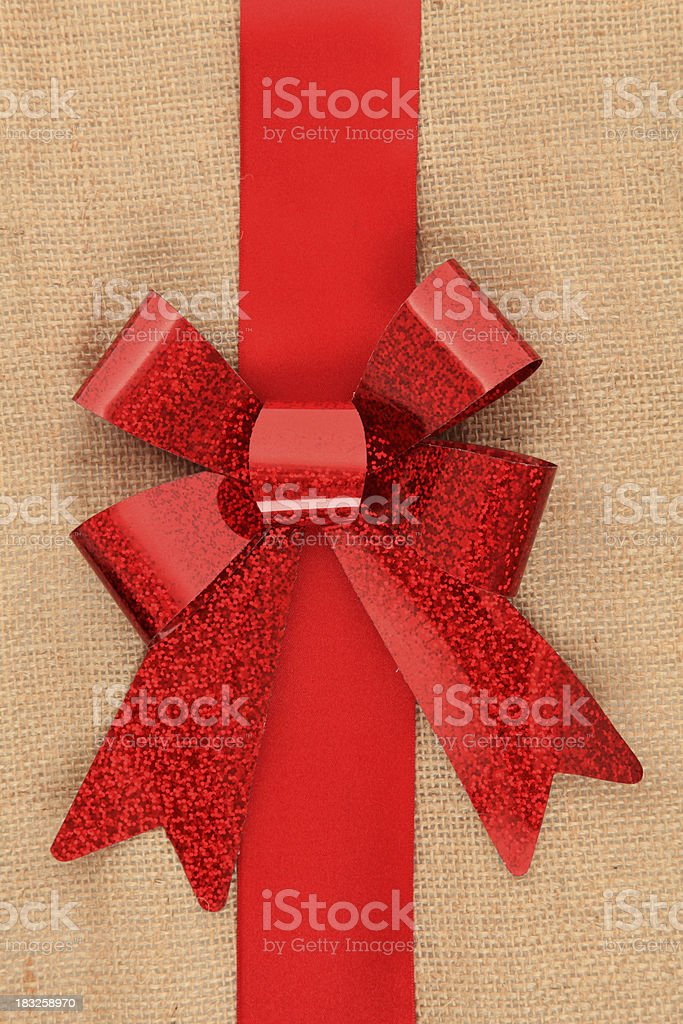 Red gift bow on hessian background royalty-free stock photo