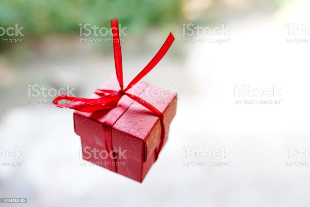 red gift box on light background with copy space, surprise for...