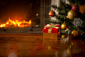 Closeup image of red gift box on wooden table in front of burning fireplace and Christmas tree