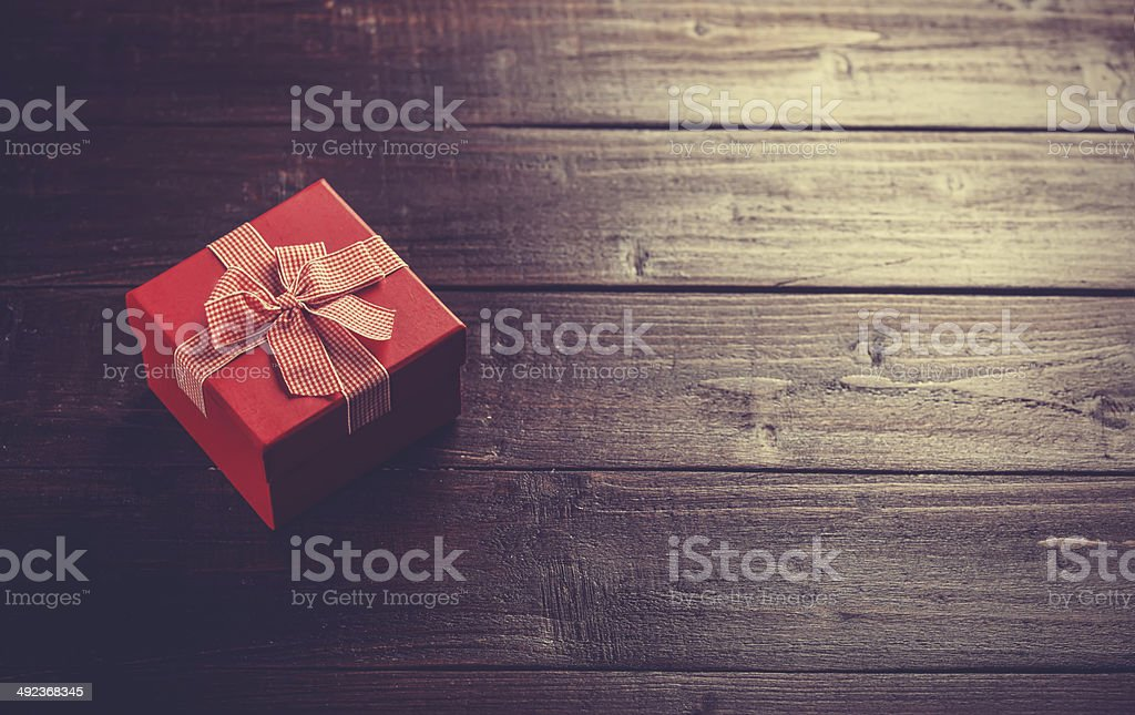 Red gift box on wooden table. stock photo