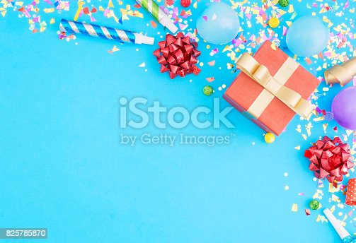 istock Red gift box various party confetti, balloons, on blue background with border. Flat lay 825785870