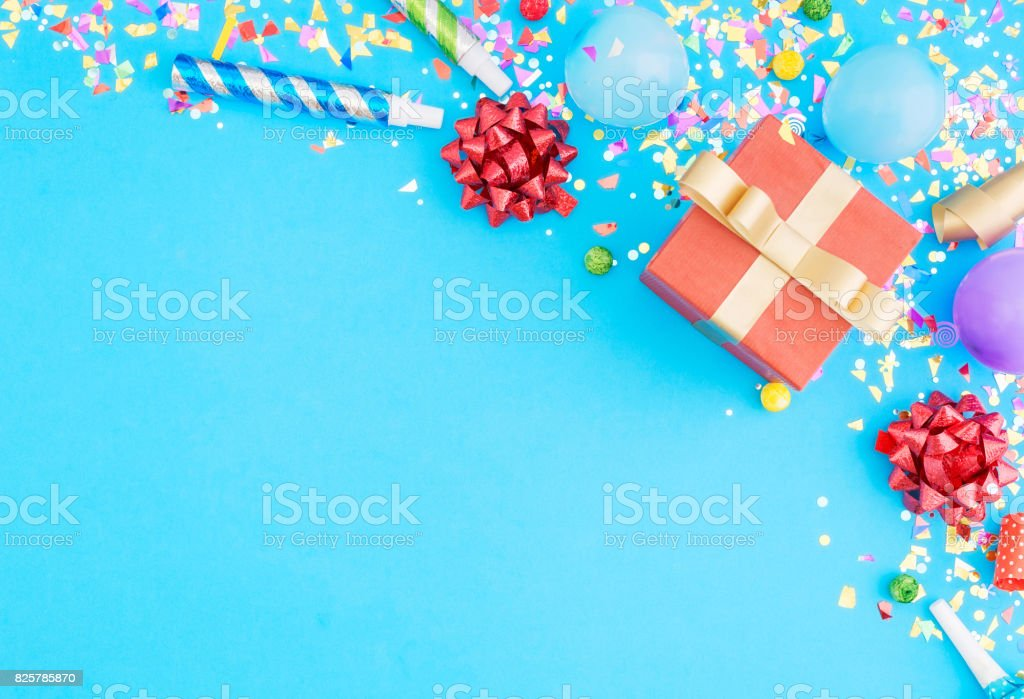 Red gift box various party confetti, balloons, on blue background with border. Flat lay stock photo