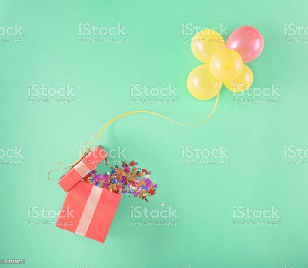 Red gift box with and set of balloons on a light background stock photo