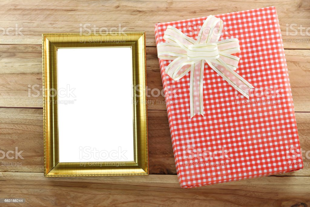 Red gift box with empty wooden picture frame on wood background. royalty-free 스톡 사진