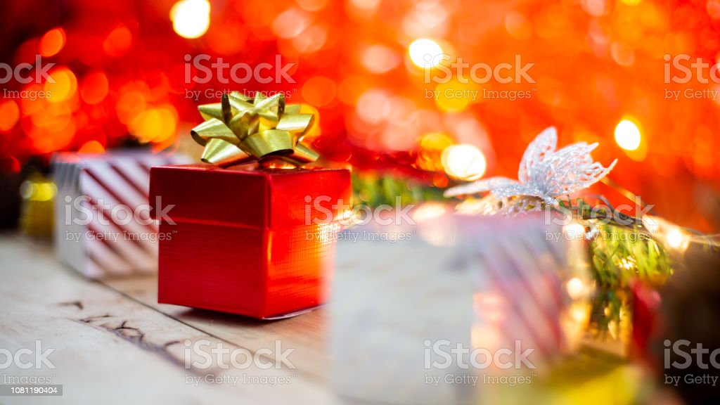 Red gift box with gold ribbon and bow with gift and christmas...