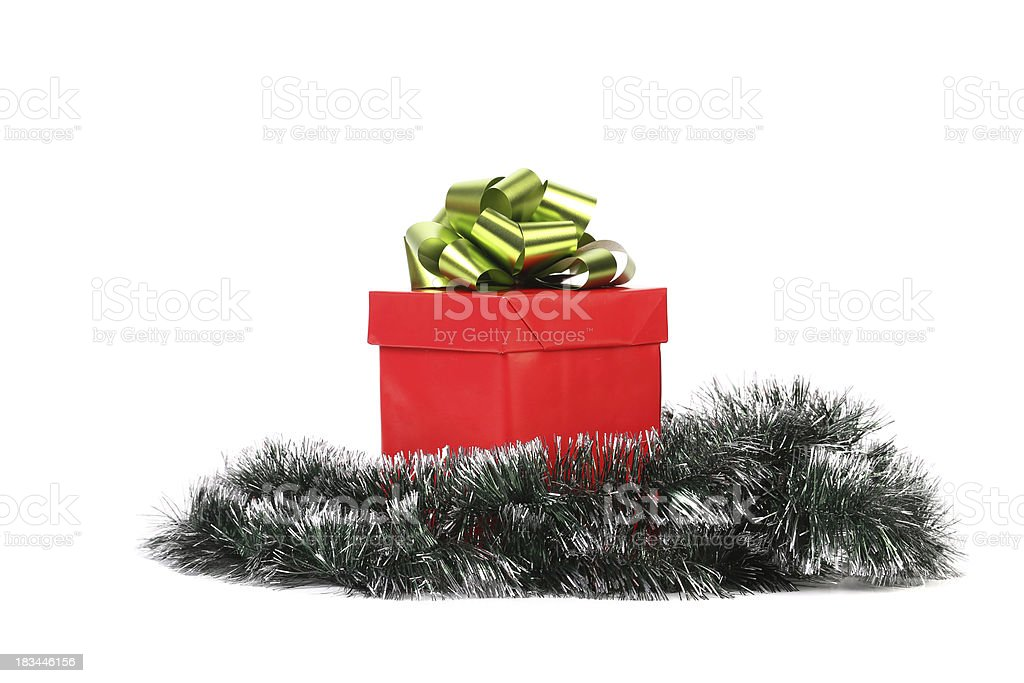 Red gift box with green-golden bow and tinsel. royalty-free stock photo