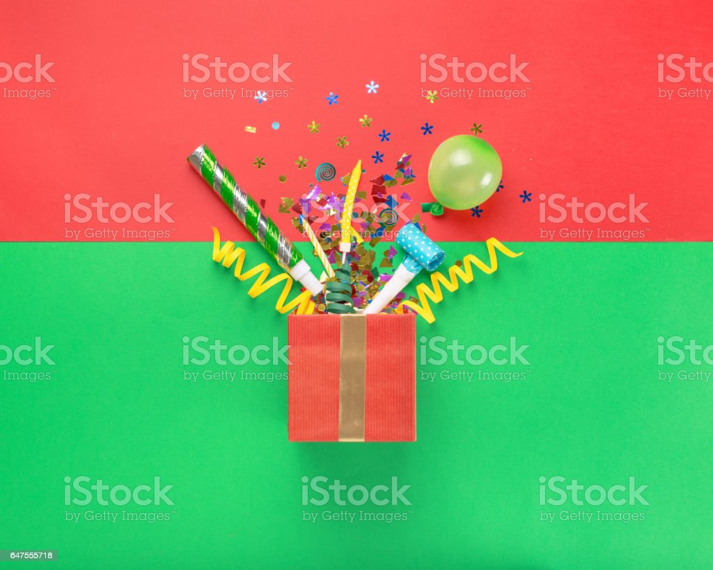 Red gift box with various party confetti, balloons, streamers, noisemakers and decoration on a multicolored background stock photo