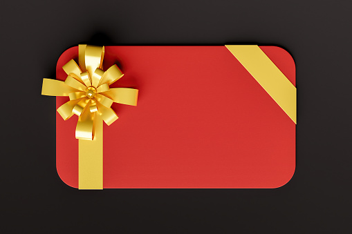 red gift card with gold ribbon on black background